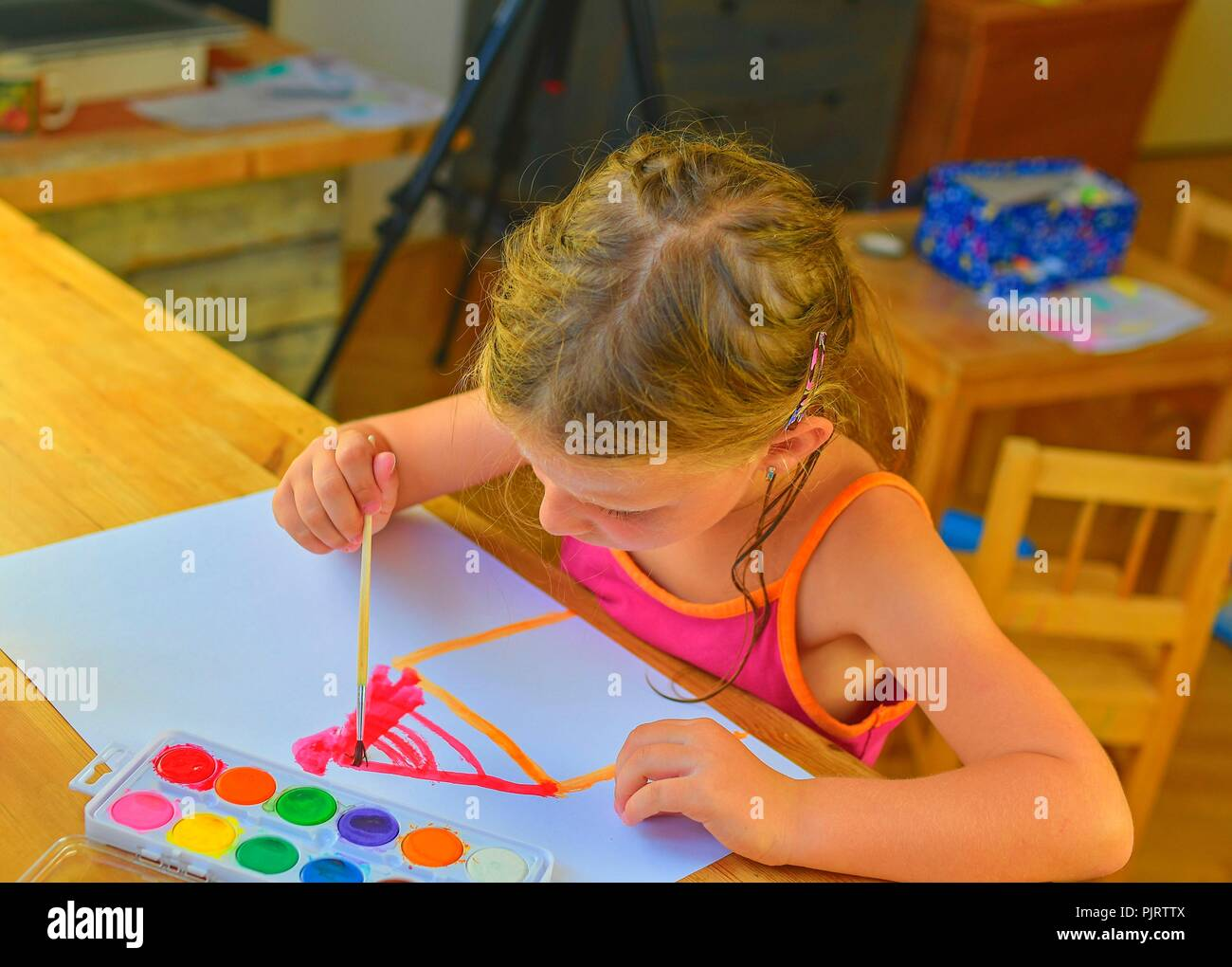 Cute little girl painting picture of house. Mortage concept Stock Photo