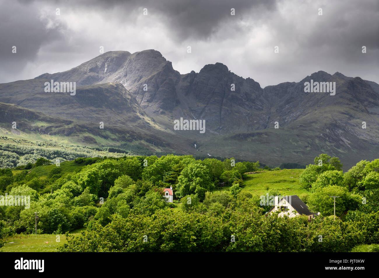 Sun on Bla Bheinn peak outlier of Black Cuillin Hills under dark clouds from Torrin Scottish Highlands Isle of Skye Scotland UK - Stock Image