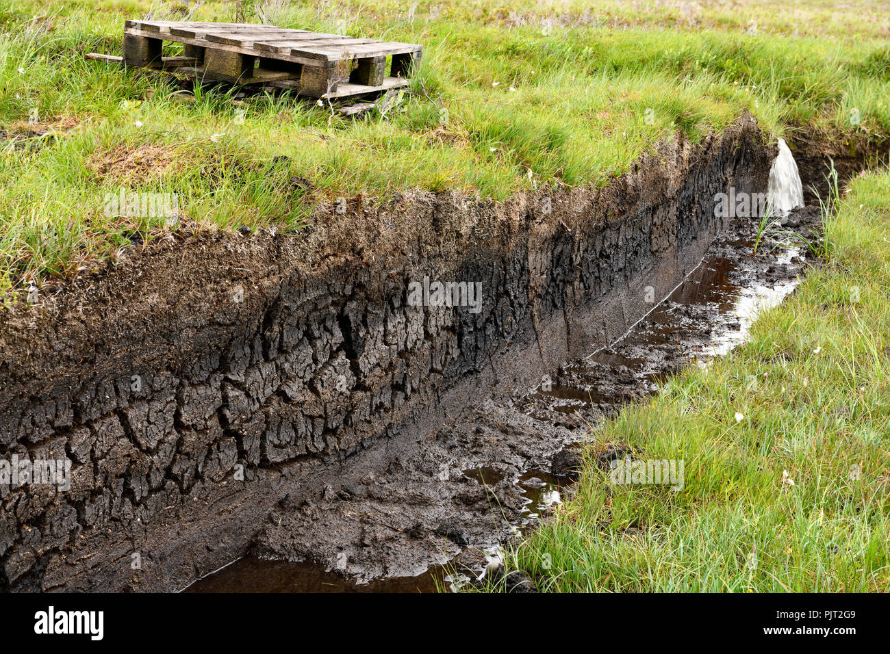 Trench cut into deep Peat of wetland moors on Isle of Skye Scotland to drain water for harvest - Stock Image