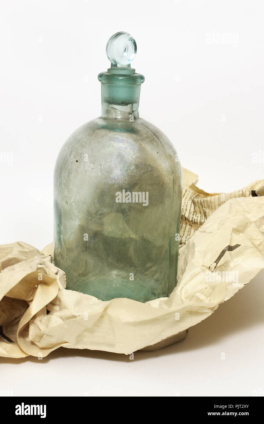 vintage bottle. chemical vessel, corked glass stopper, was wrapped in crumpled newspaper sheet - Stock Image