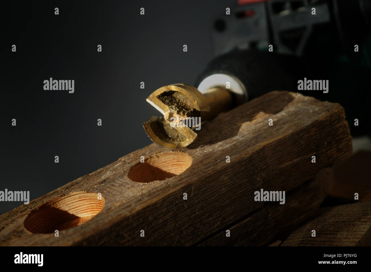 Close up on small metal tool for drilling circular holes sitting on top of wooden block over black background - Stock Image