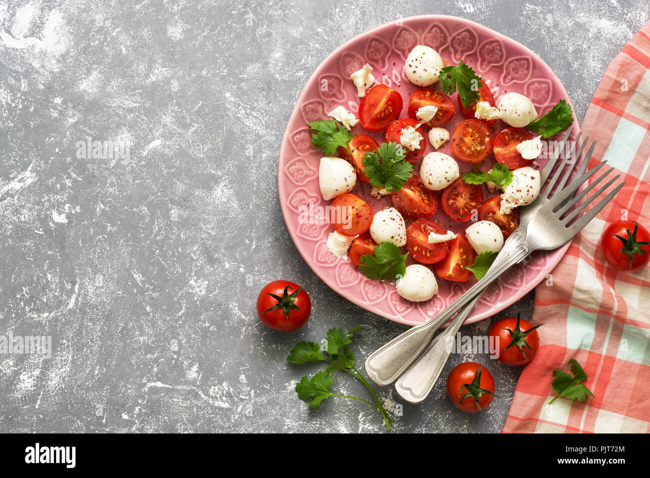 Fresh salad with mozzarella and tomatoes on a grey background, checkered napkin and forks. - Stock Image