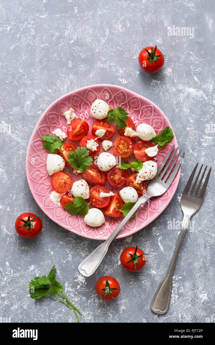Mozzarella and cherry tomatoes are served on a pink plate. Gray background, top view. - Stock Image