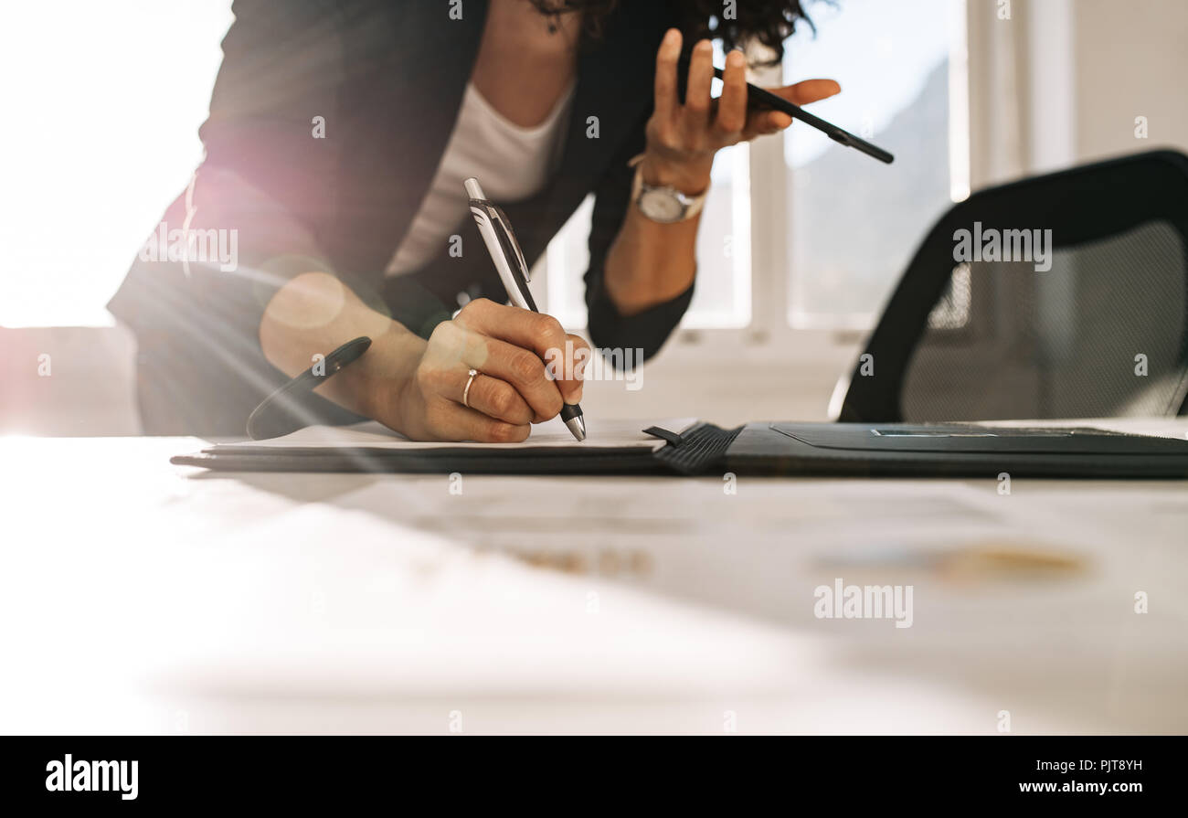 Woman entrepreneur making notes standing at her table in office while holding a cell phone in hand. Close up of a businesswoman writing in diary leani - Stock Image