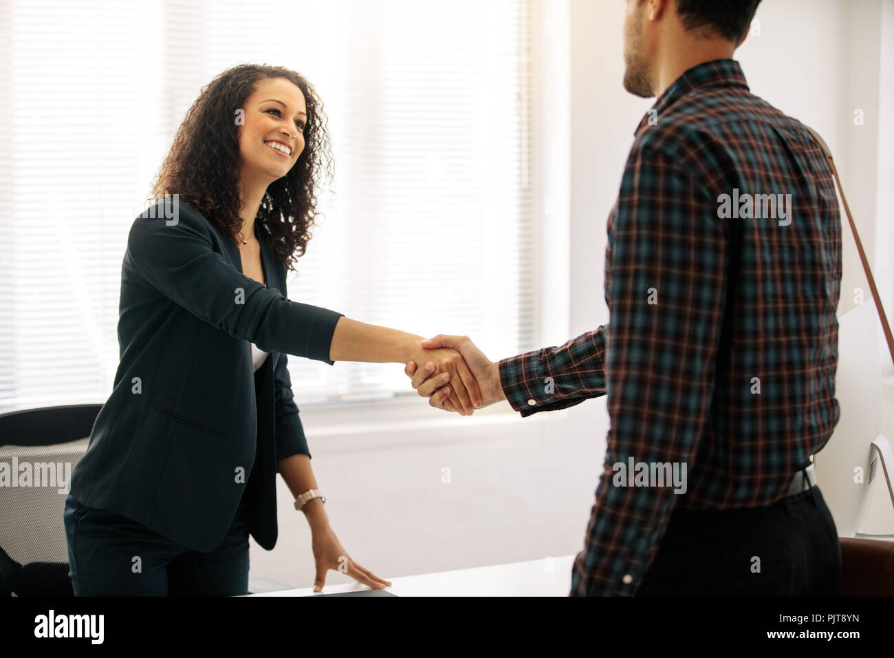 Business partners meeting in office shaking hand. Woman entrepreneur in formal clothes greeting a businessman at her table in office. - Stock Image