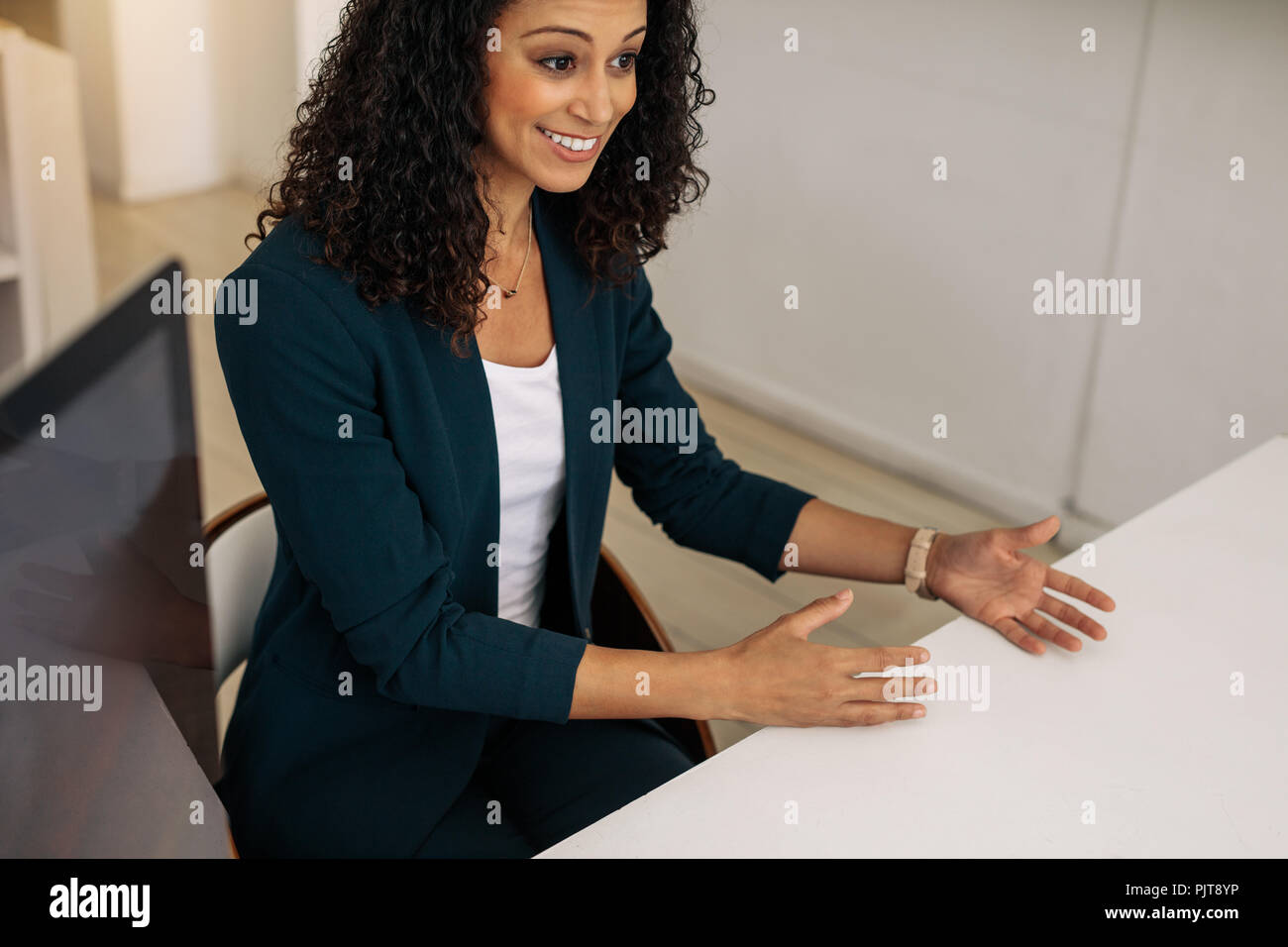 Smiling Businesswoman Sitting In Office Making Hand Gestures