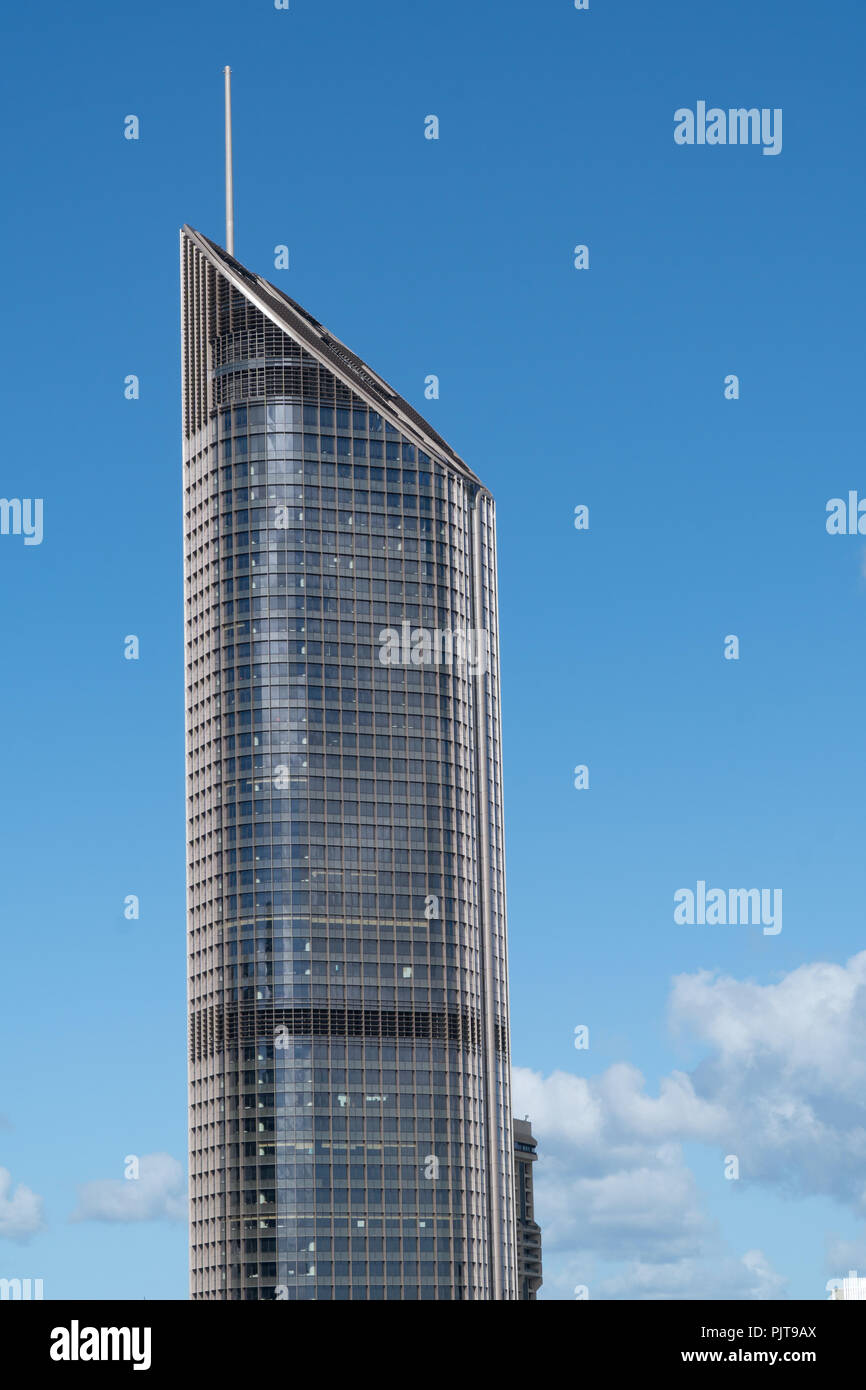 The upper half of a skyscraper against blue sky in Brisbane - Stock Image