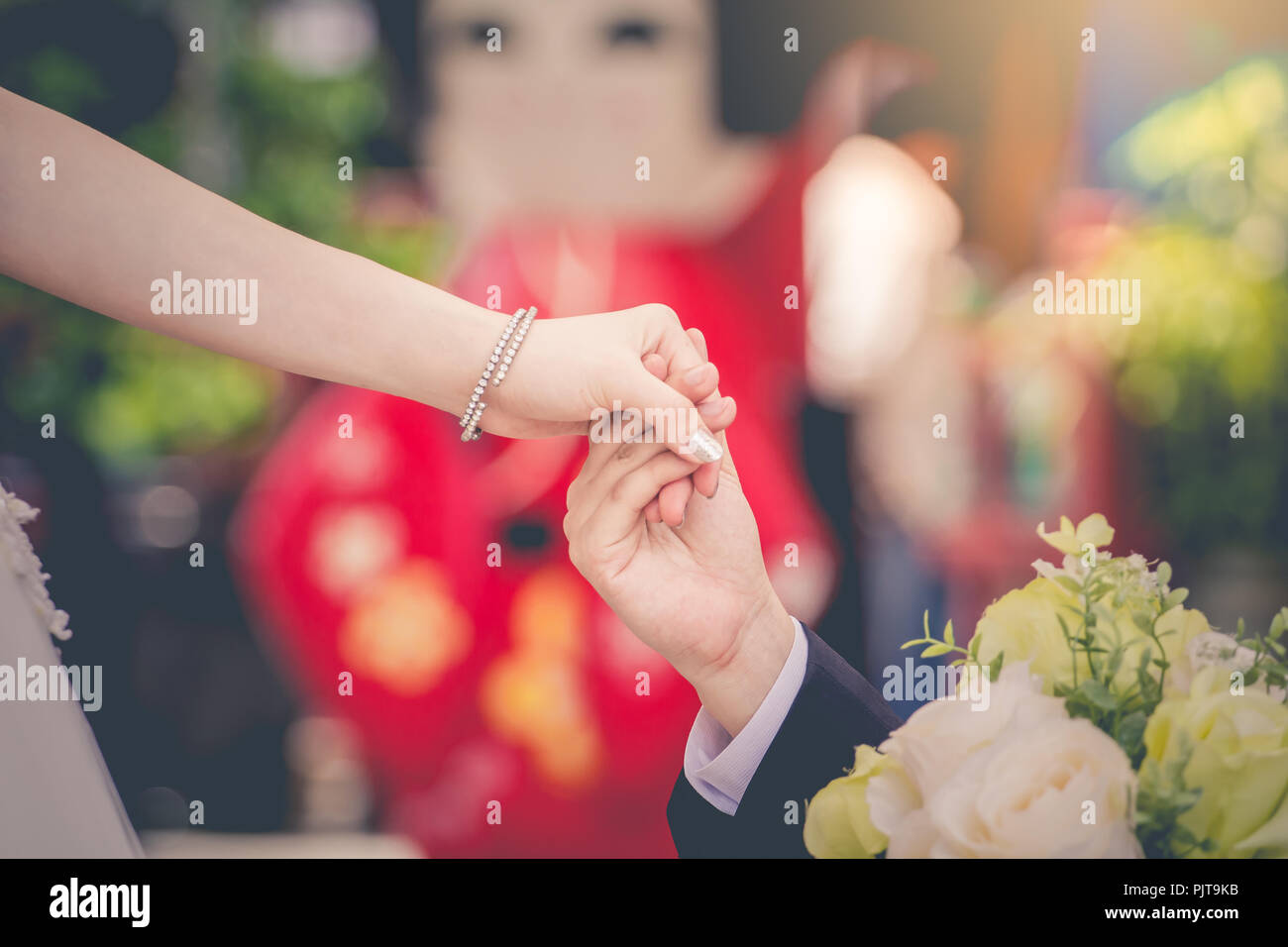 Young express love with a handshake as a symbol of love and marriage. - Stock Image