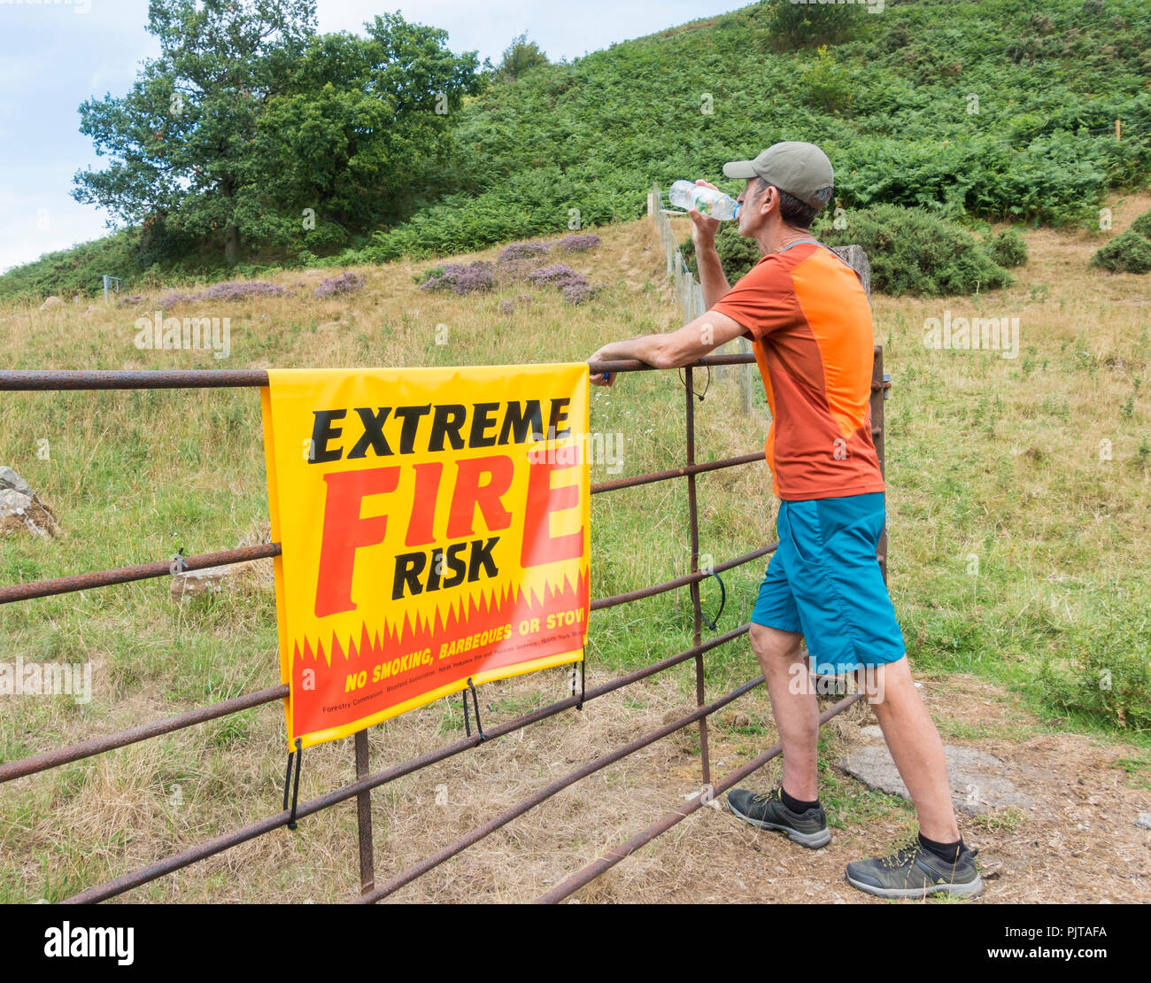 Heatwave UK: Trail runner next to Extreme fire risk sign in The North York Moors National Park. Summer 2018 - Stock Image