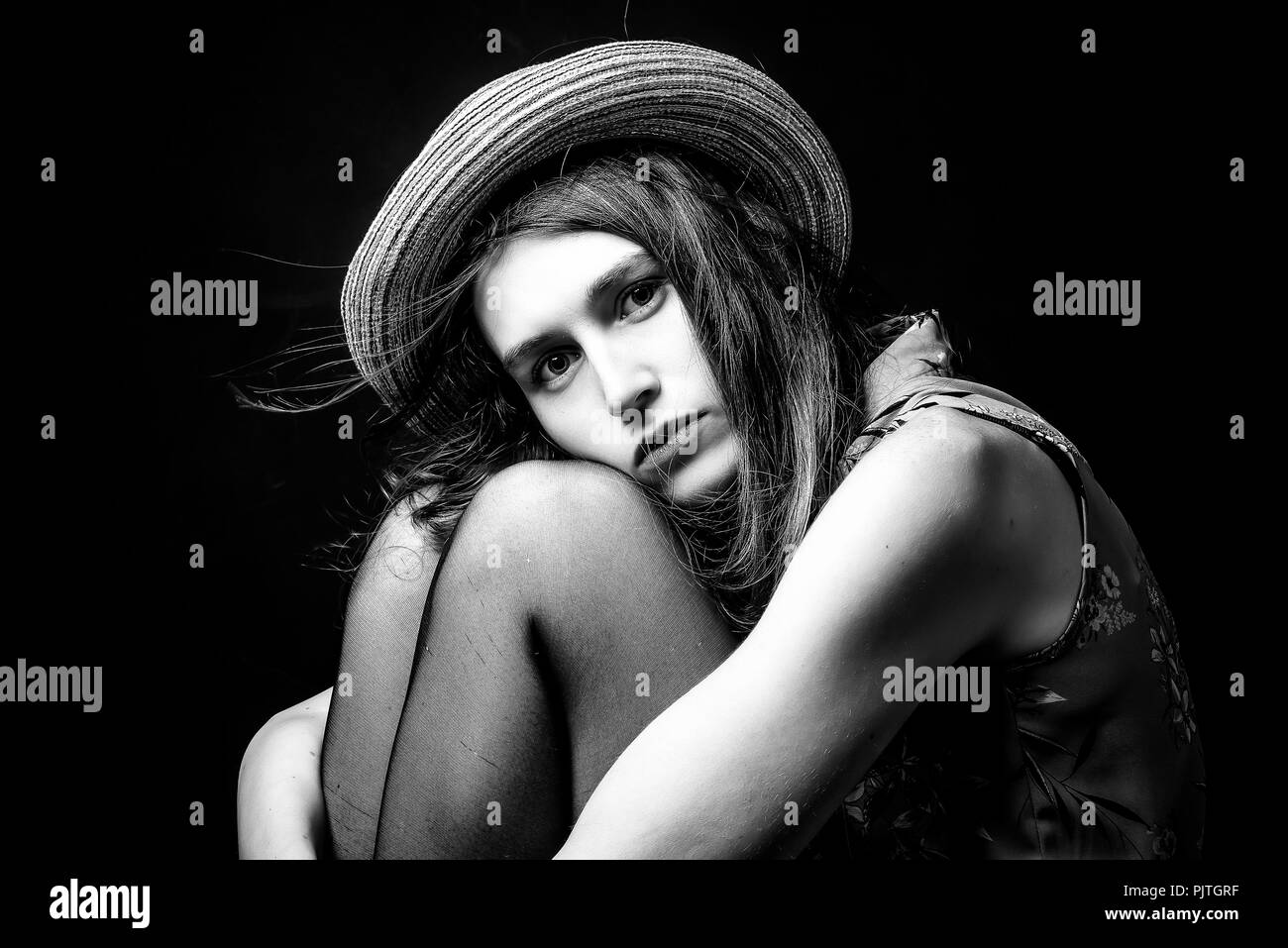 Studio image of a young woman sitting on a stool hugging her knees in a depressed frame of mind - Stock Image