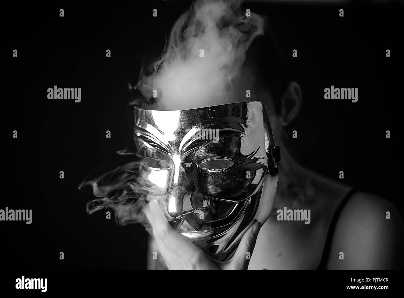 Studio portrait of a woman hiding her face with an anonymous style mask with smoke omitting from behind - Stock Image
