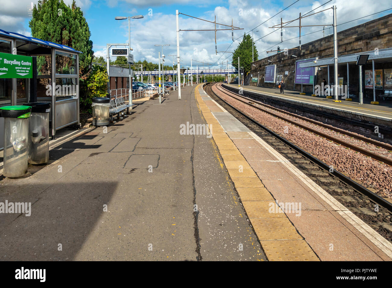 Two of the platforms and rail tracks at Motherwell Station in North Lanarkshire, Scotland. Two waiting pasengers, seats, car park, recycling bins, clo - Stock Image