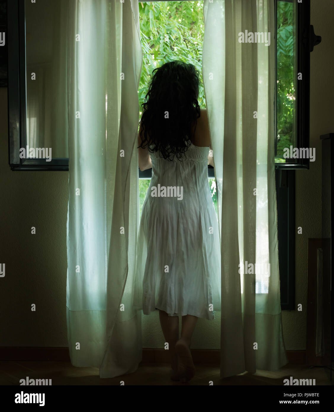 Woman in white dress looking out the window, Woman looking out the window - Stock Image