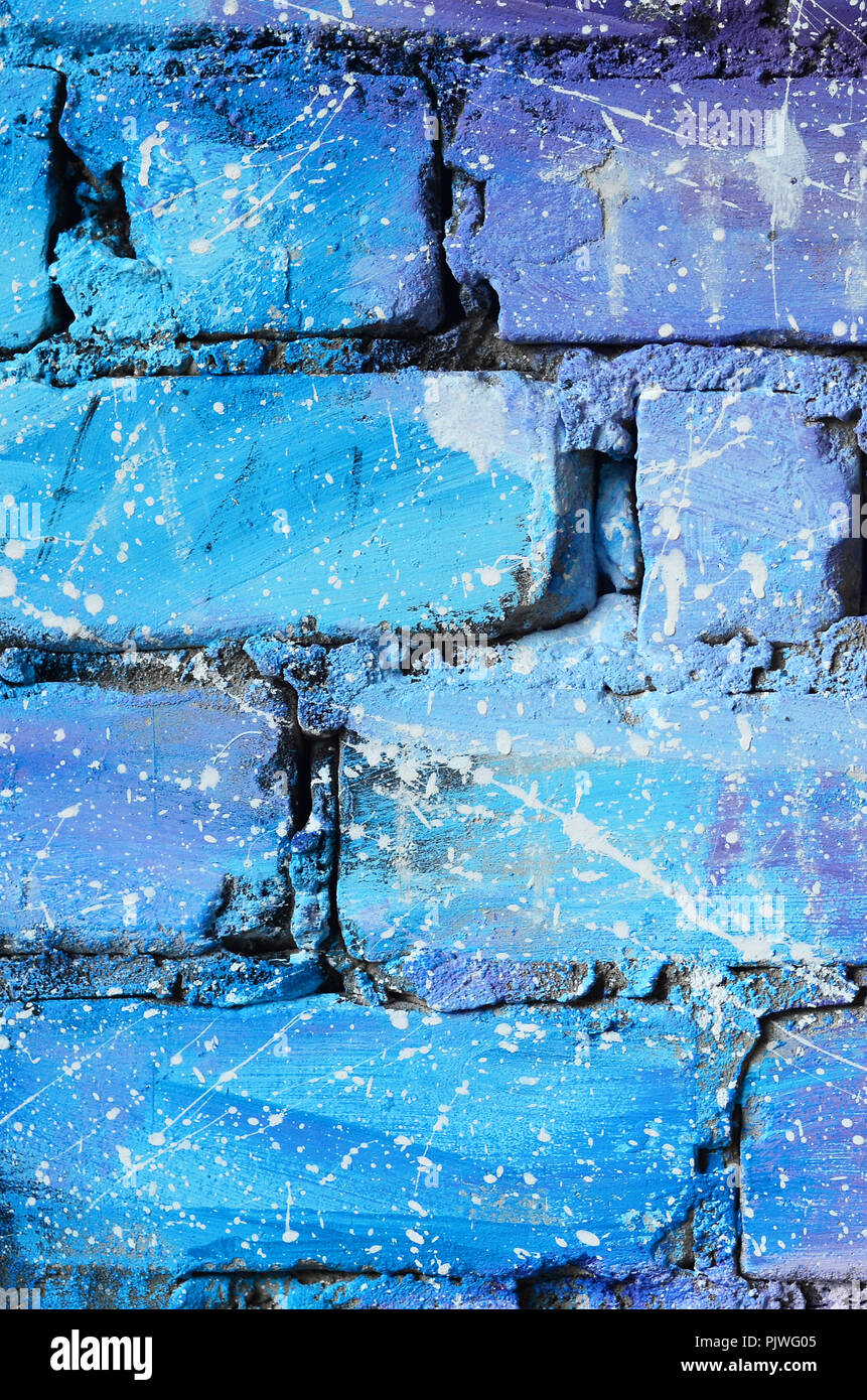 The texture of the old brick wall, painted in blue and purple colors with carelessly spaced white drops and splashes that visualize the stars in outer - Stock Image