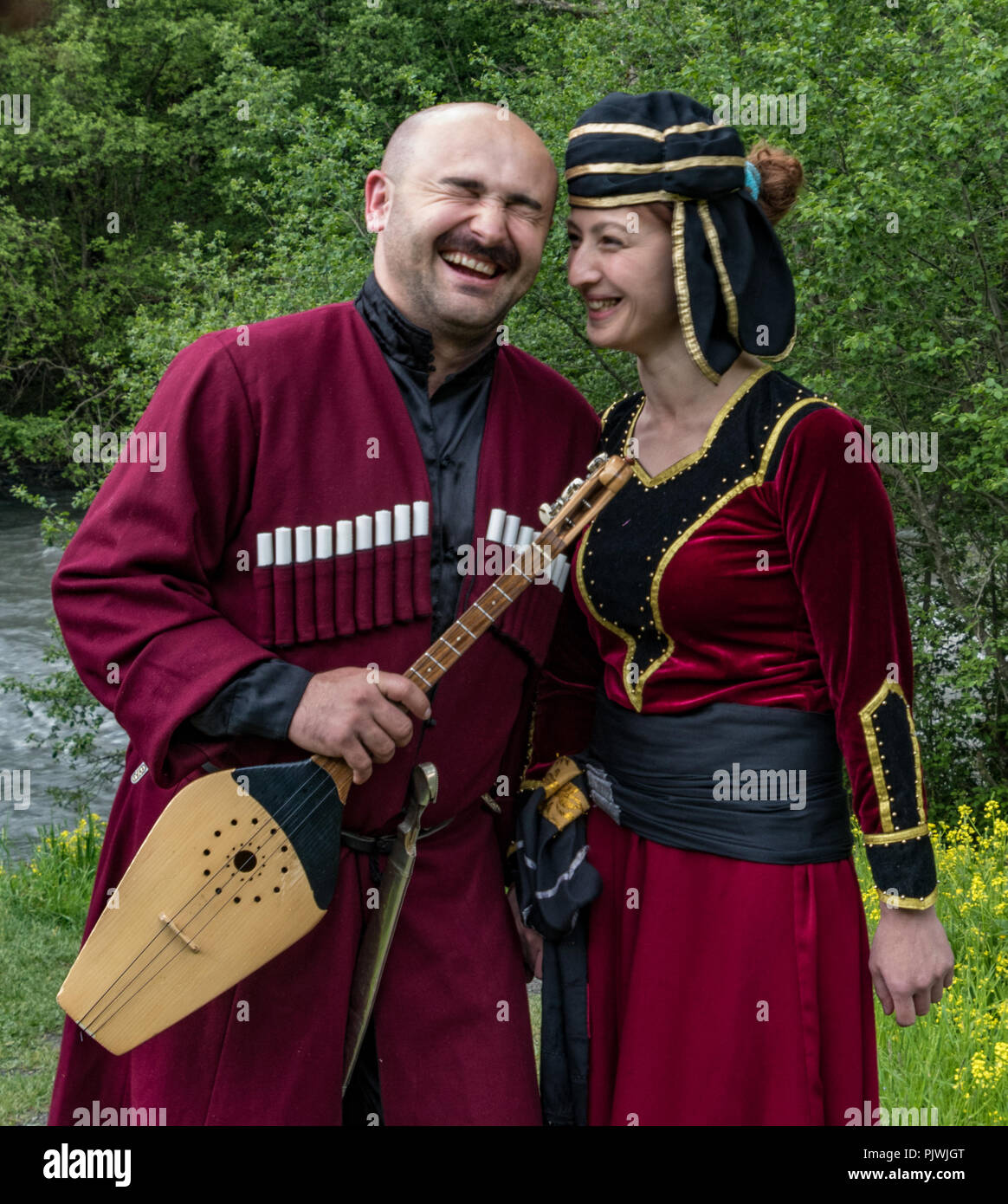 Mestia, Georgia / June 11, 2016 - Man and woman in traditional medieval garb share a laugh while holding a musical stringed instrument - Stock Image