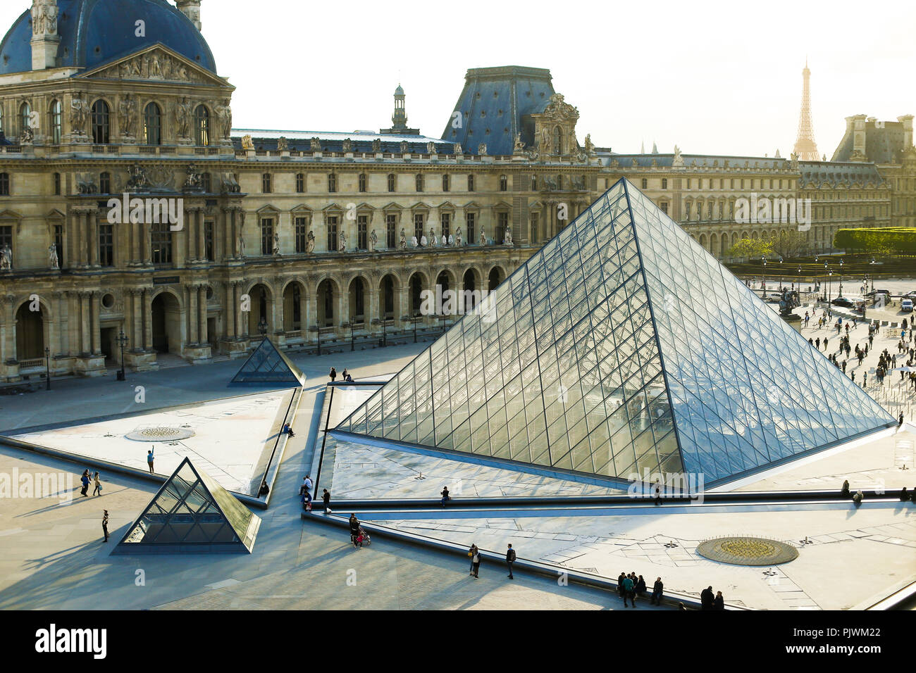 People walking in Louvre near glass pyramid, Paris, France. - Stock Image