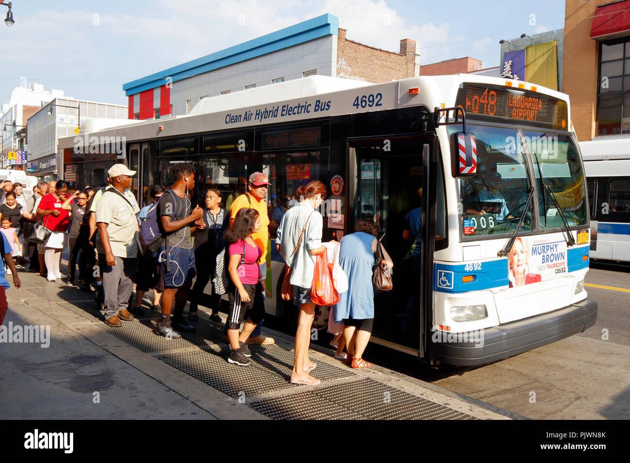 New Yorkers queue to board a NYC Transit bus in Flushing, New York. Stock Photo