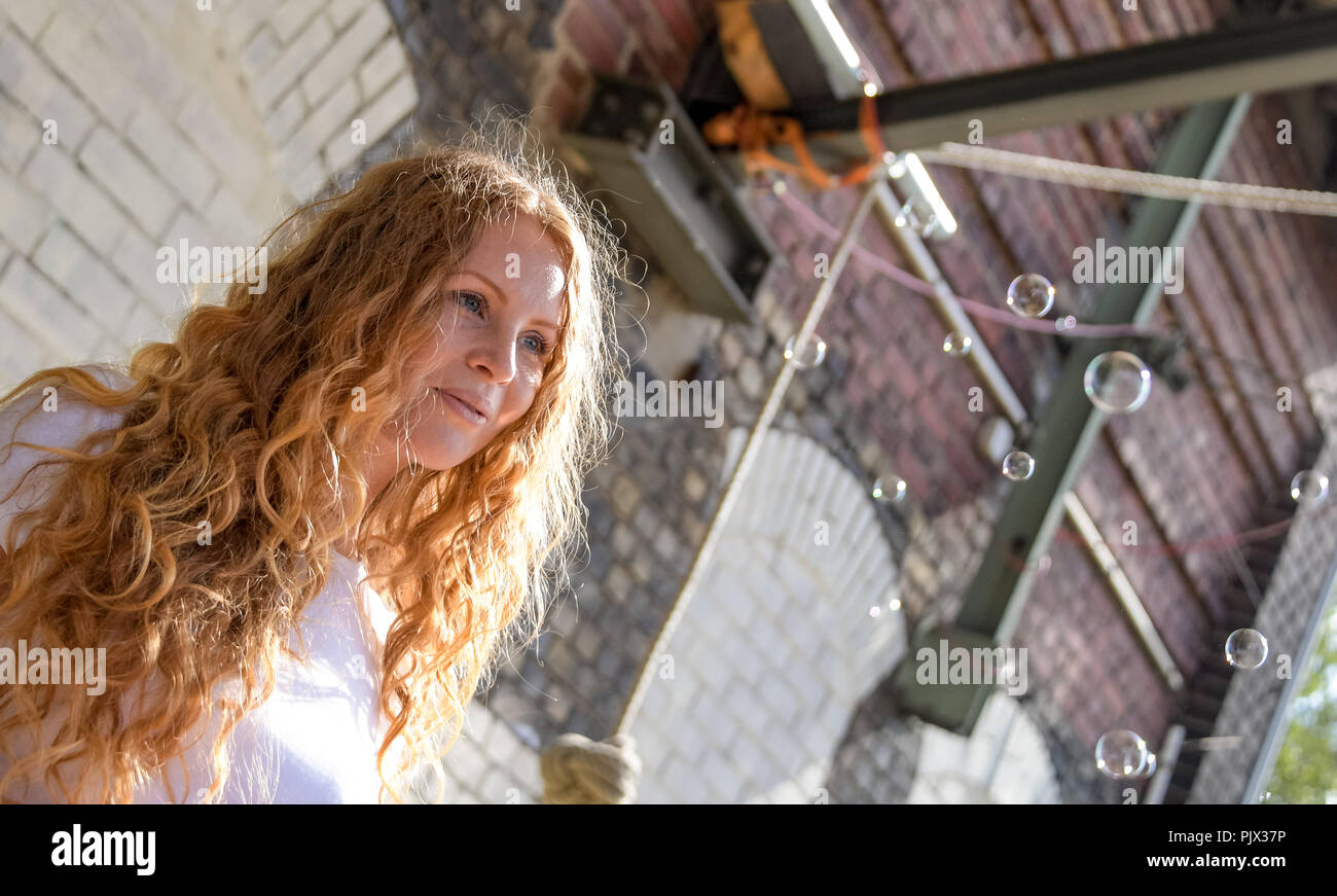 Hamburg, Germany. 09th Sep, 2018. 09.09.2018, Hamburg: Lisa (27) looks after some soap bubbles at the meeting of red-haired people from all over Germany. About 150 million people in the world have red hair. Natural red hair is rare, at most two percent of the world's population are real Redheads. The meeting of redheaded people from all over Germany is organized by the editor of the 'Magazine for redheads'. Credit: Axel Heimken/dpa/Alamy Live News - Stock Image
