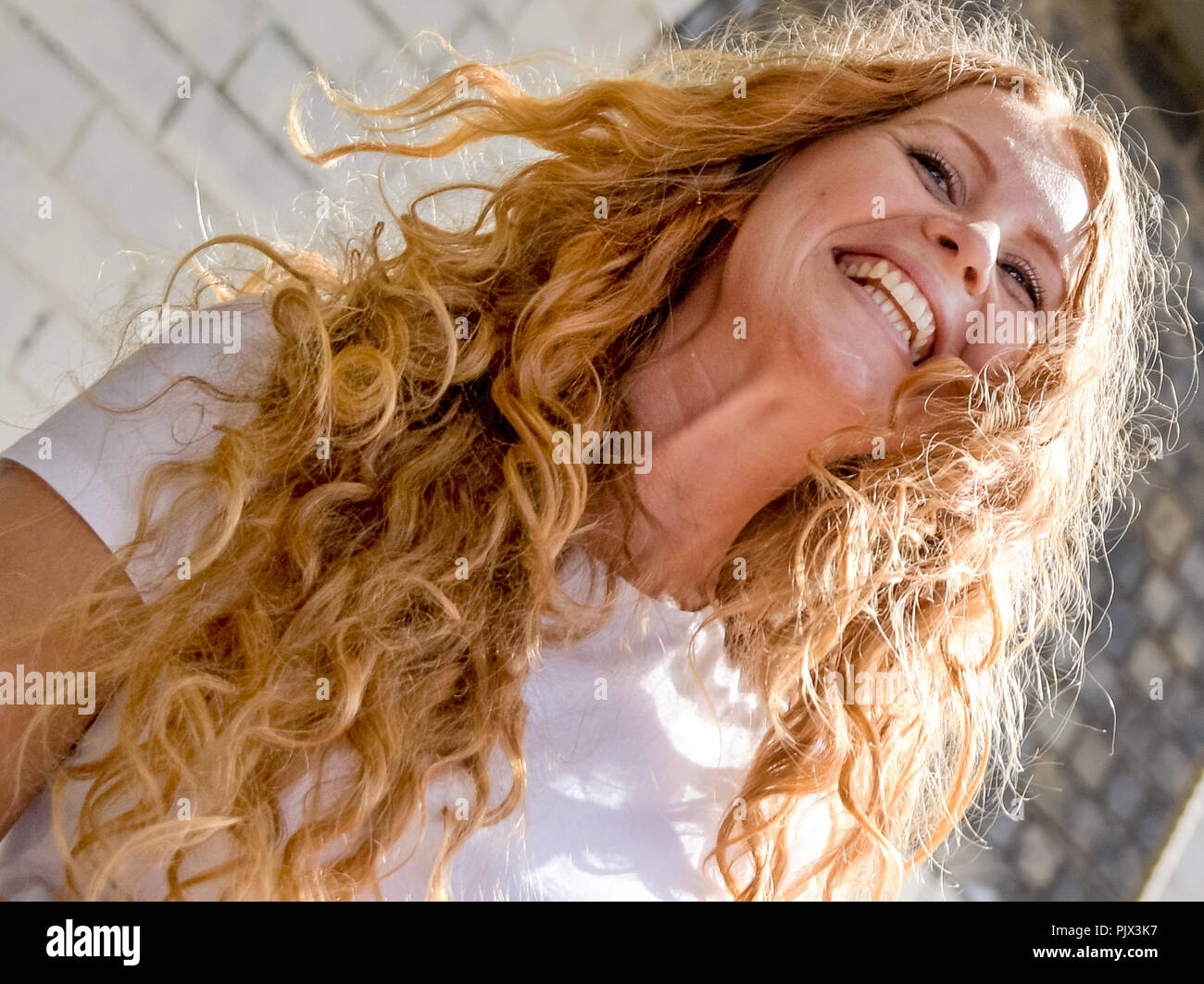 Hamburg, Germany. 09th Sep, 2018. 09.09.2018, Hamburg: Lisa (27) laughs at the end of the meeting of redheaded people from all over Germany. Natural red hair is rare, at most two percent of the world's population are real Redheads. The meeting of redheaded people from all over Germany is organized by the editor of the 'Magazine for redheads'. Credit: Axel Heimken/dpa/Alamy Live News - Stock Image