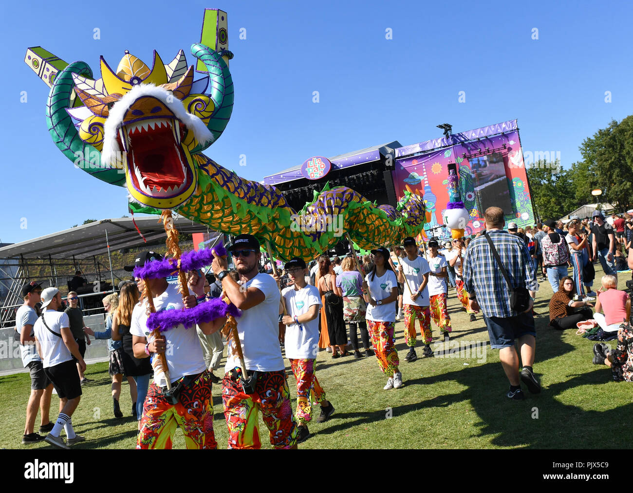 09.09.2018, Berlin: Performers wear a large colorful dragon figure at the two-day music festival Lollapalooza across the grounds of the Olympic Park. Photo: Jens Kalaene/dpa-Zentralbild/dpa - Stock Image
