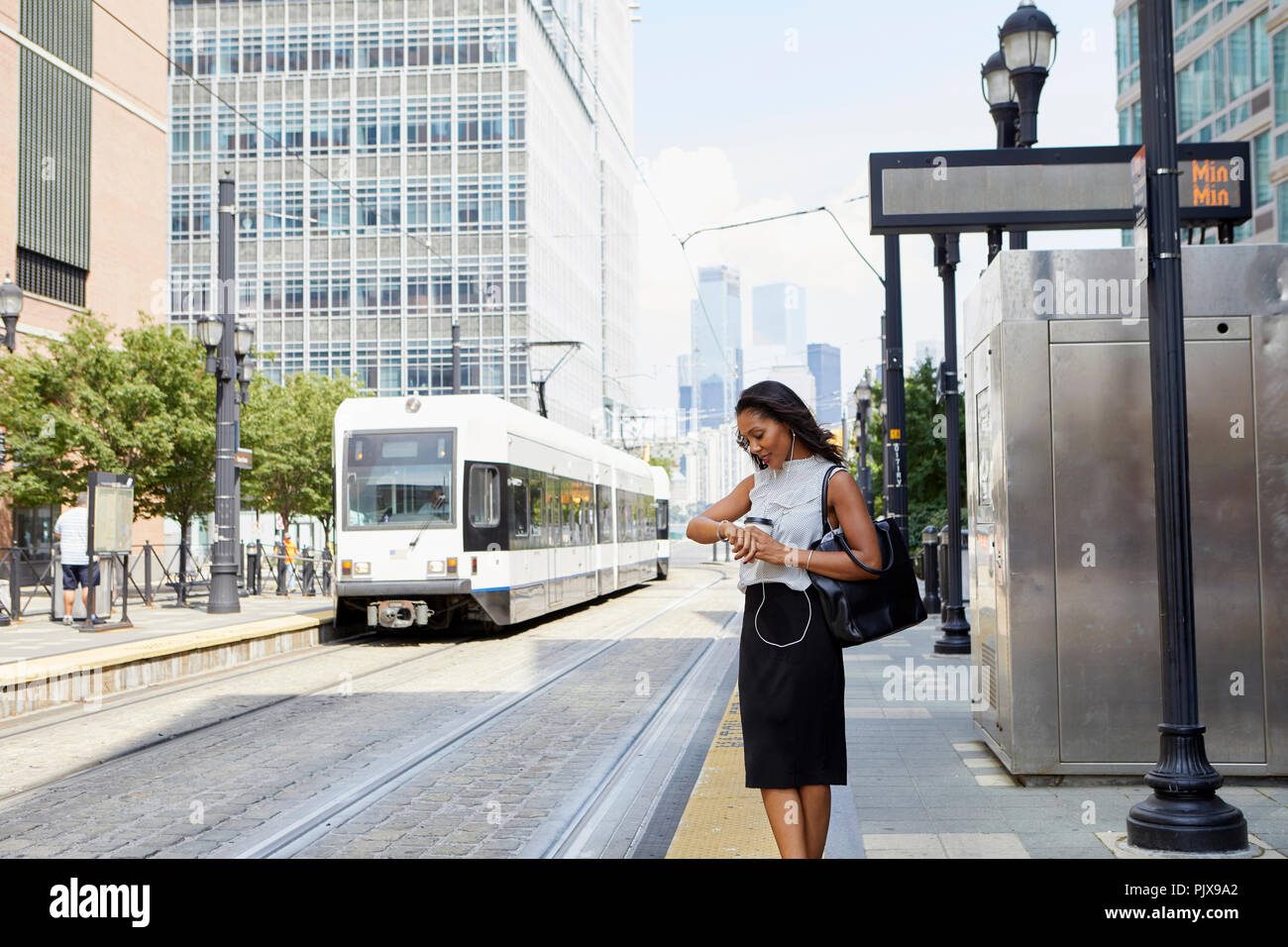 Businesswoman checking time by light rail line - Stock Image