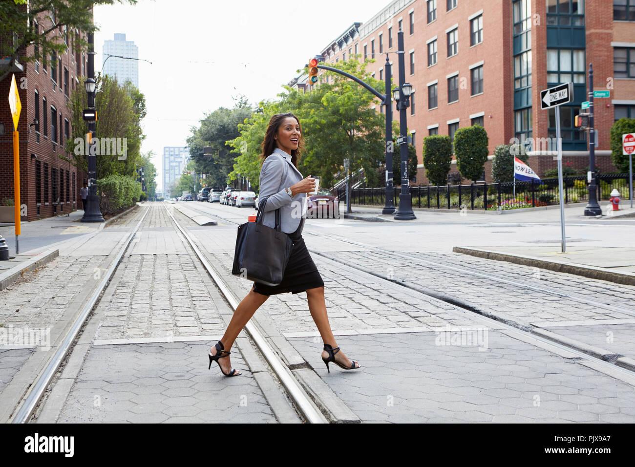 Businesswoman crossing light rail tracks - Stock Image