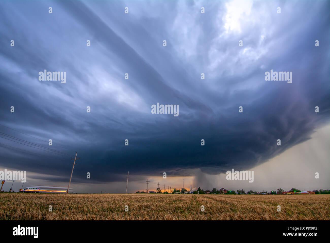 Rotating, tornado-warned storm develops pretty striations over Collyer, Kansas - Stock Image