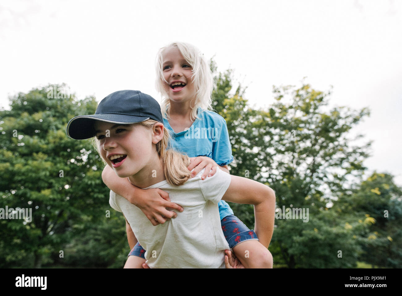 Children playing piggyback in park - Stock Image