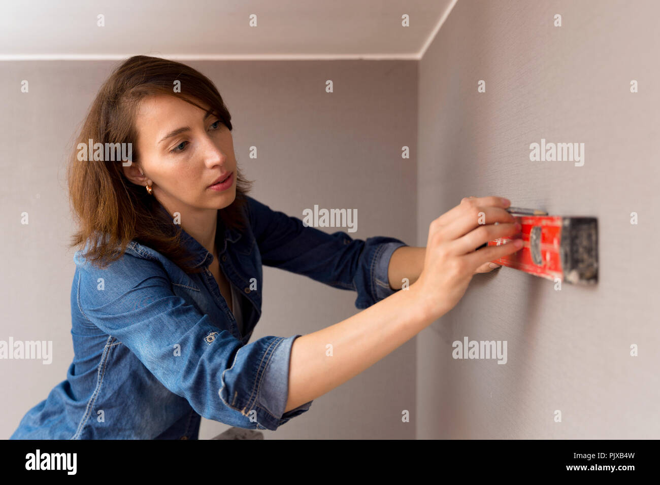 Home Improvement Beautiful Women Making A Mark On Wall With Level