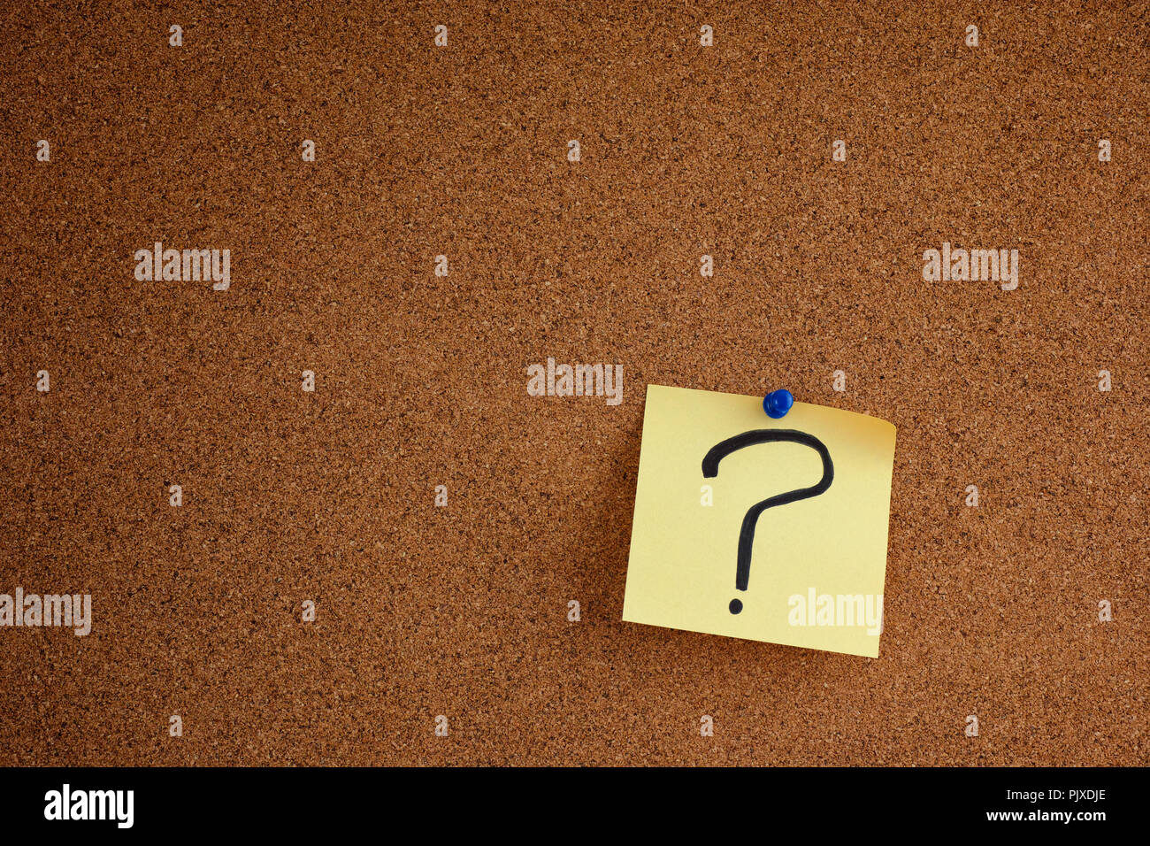 Post it note with question mark on bulletin board. Close up. - Stock Image