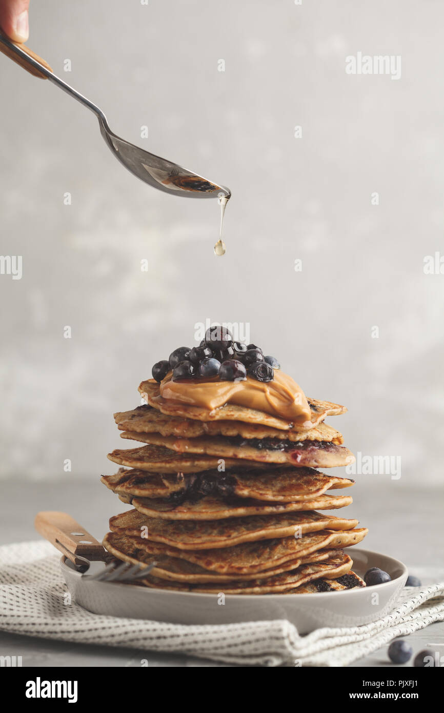 Stack vegan blueberry pancakes with peanut butter and syrup. Clean eating concept. - Stock Image