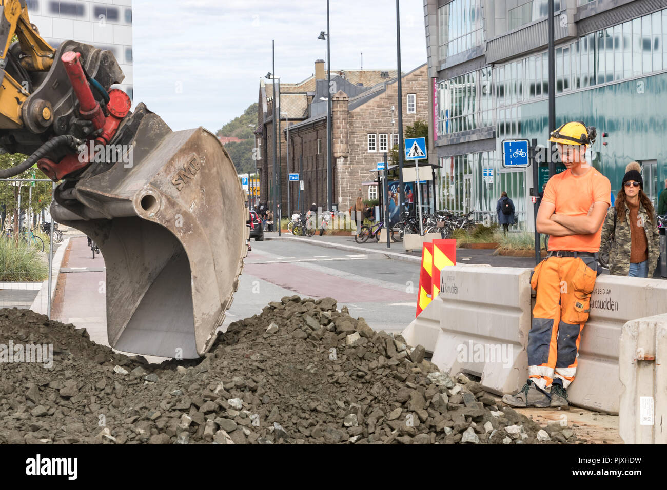 Trondheim, Norway - August 28th, 2018: A young construction worker standing watching an excavator machine at Brattorkaia St, wearing a helmet and a ra - Stock Image