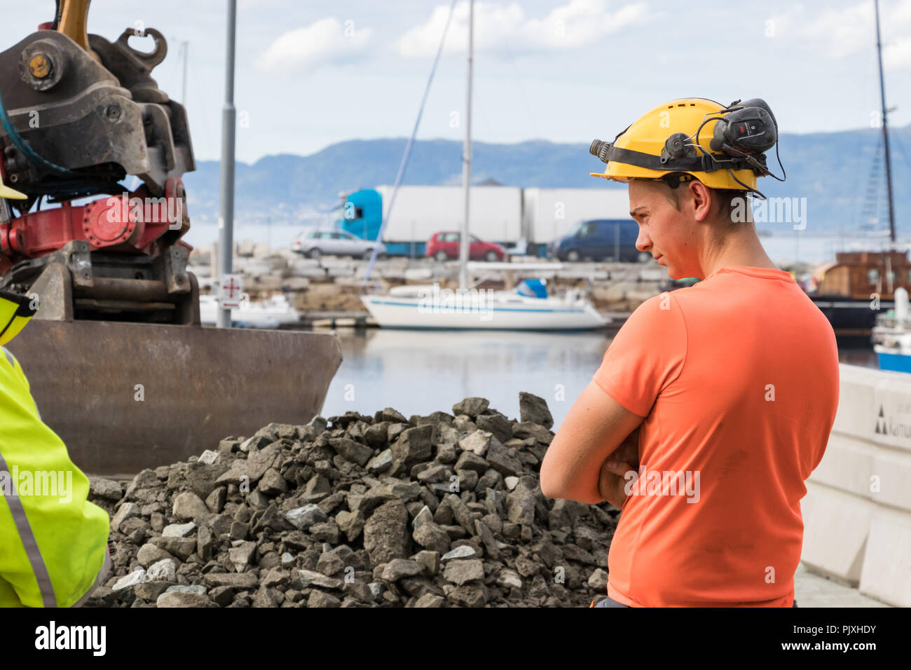 Trondheim, Norway - August 28th, 2018: A young construction worker standing at Brattorkaia St wearing a helmet and a radio hearing protection headset, - Stock Image