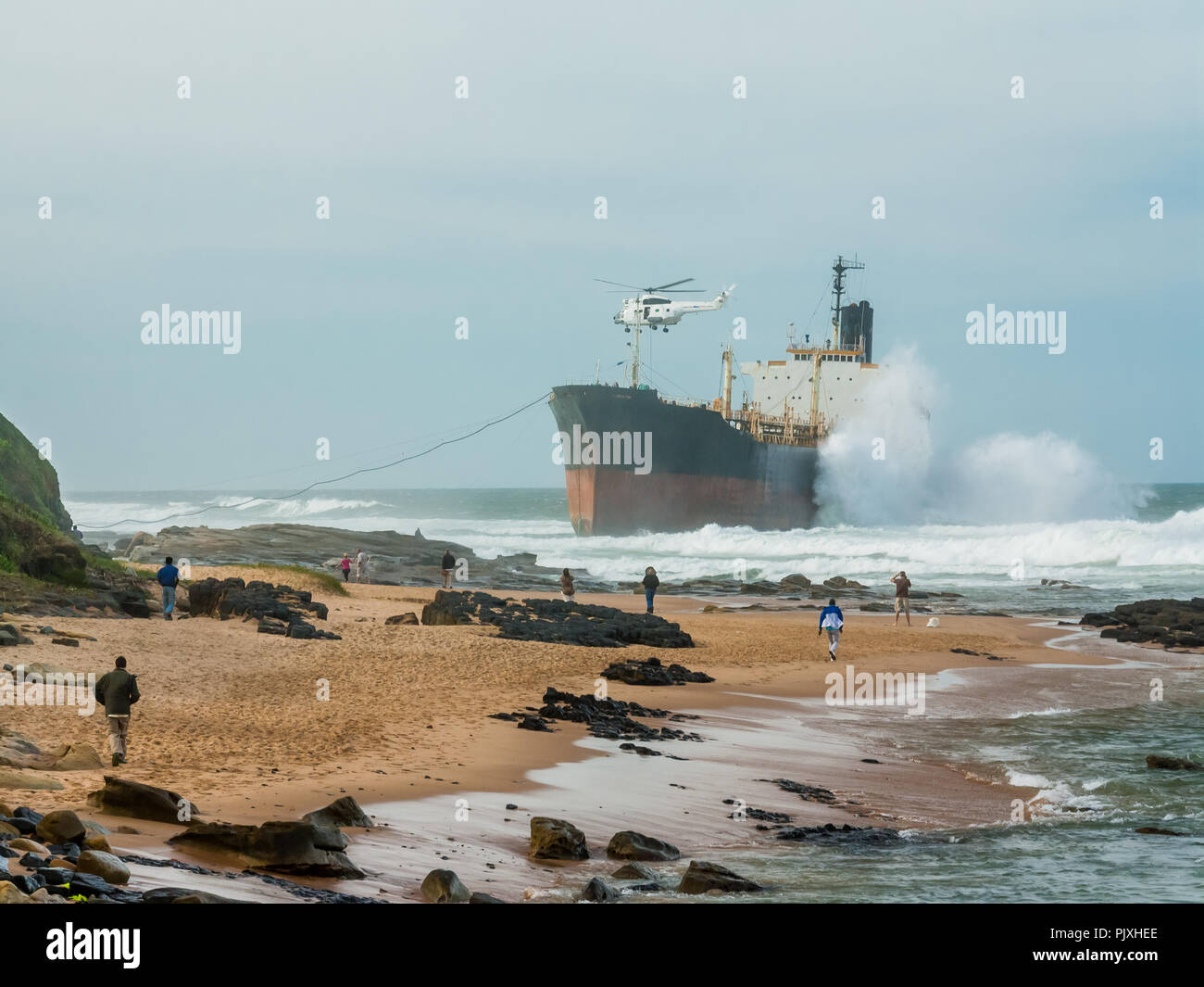 Rescue helicopter bringing supplies to the Phoenix, a derelict bulk tanker, run aground at Sheffield Beach on Durban's North Coast. - Stock Image