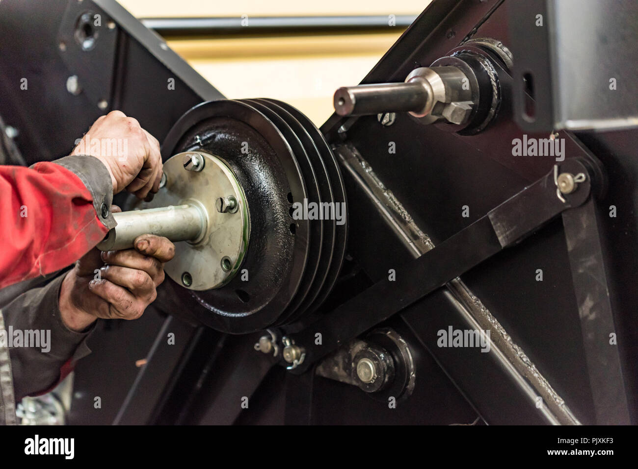 Industrial worker assembles agricultural equipment at plant - Stock Image