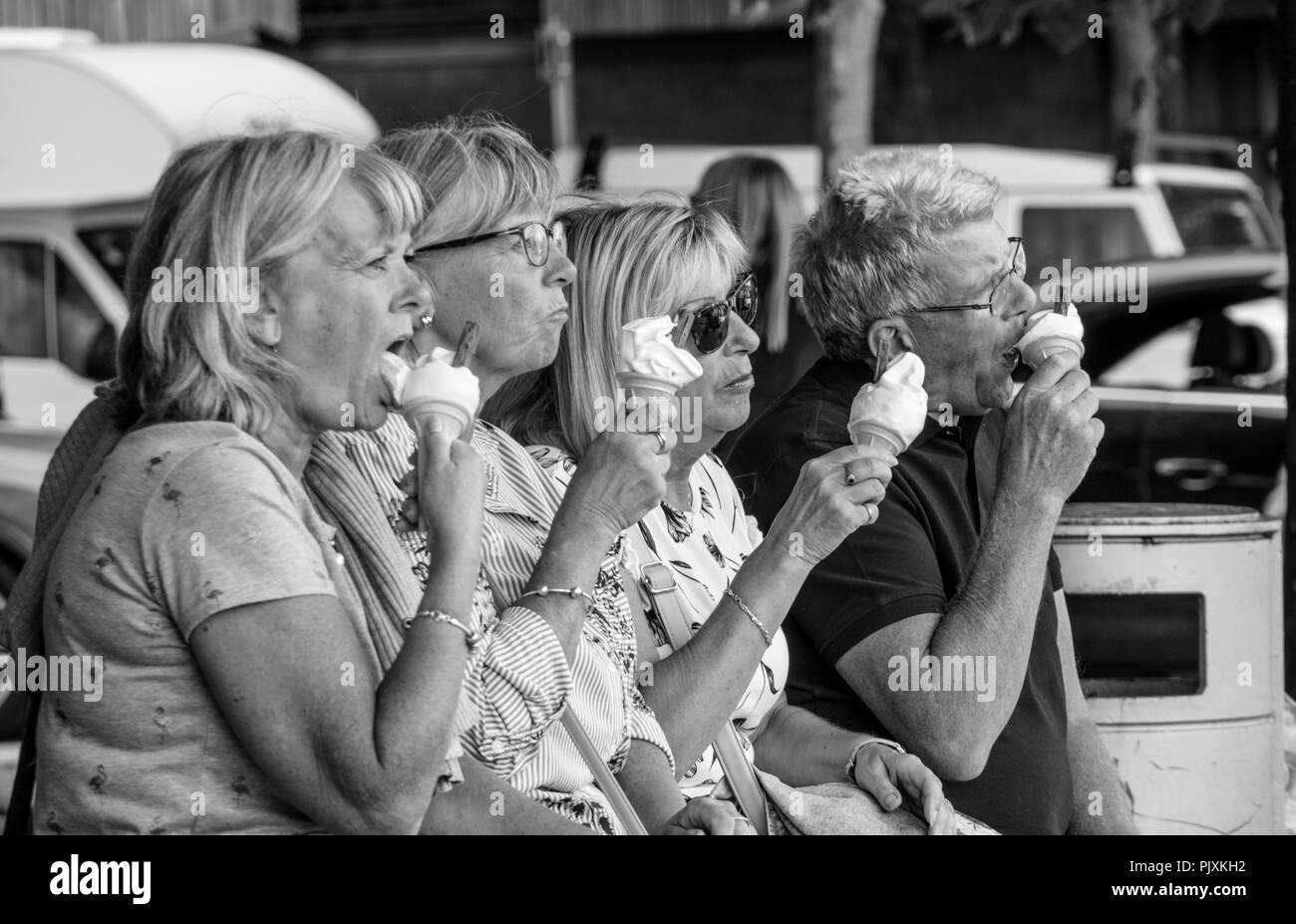 Middle aged couples eating ice creams, England, UK - Stock Image