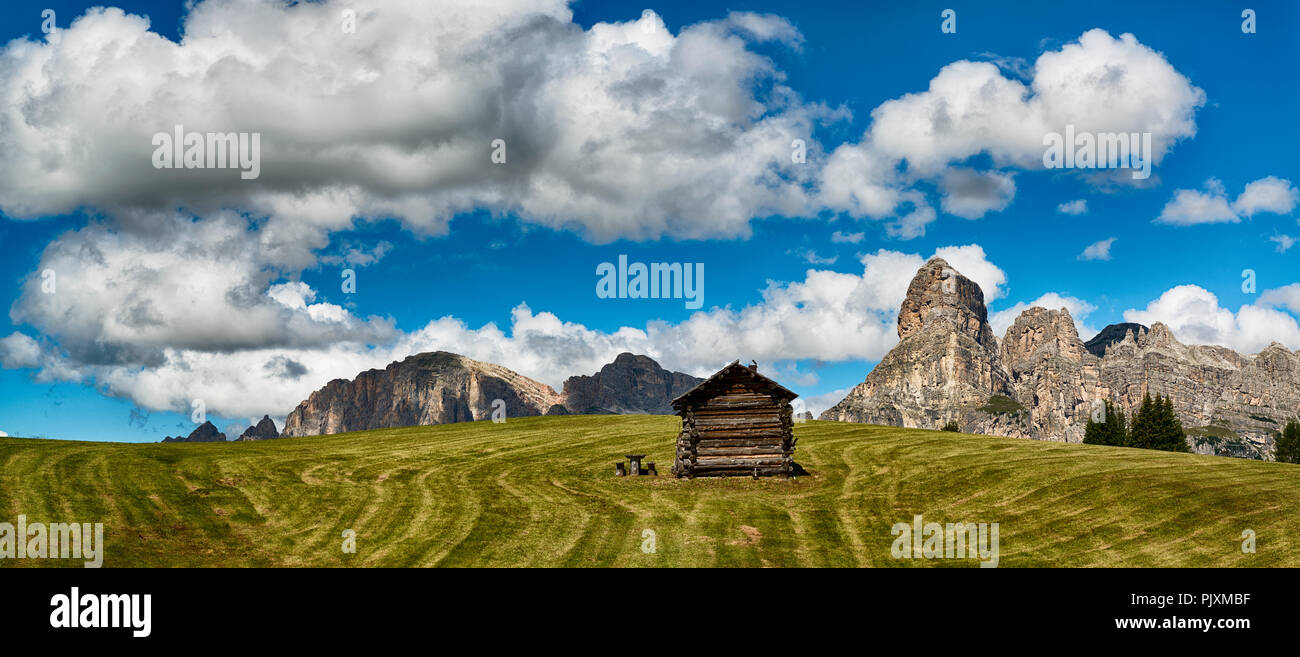 Landscape of mountains of Alta Badia in the Dolomites in summer season with green meadow in foreground, Italy - Stock Image
