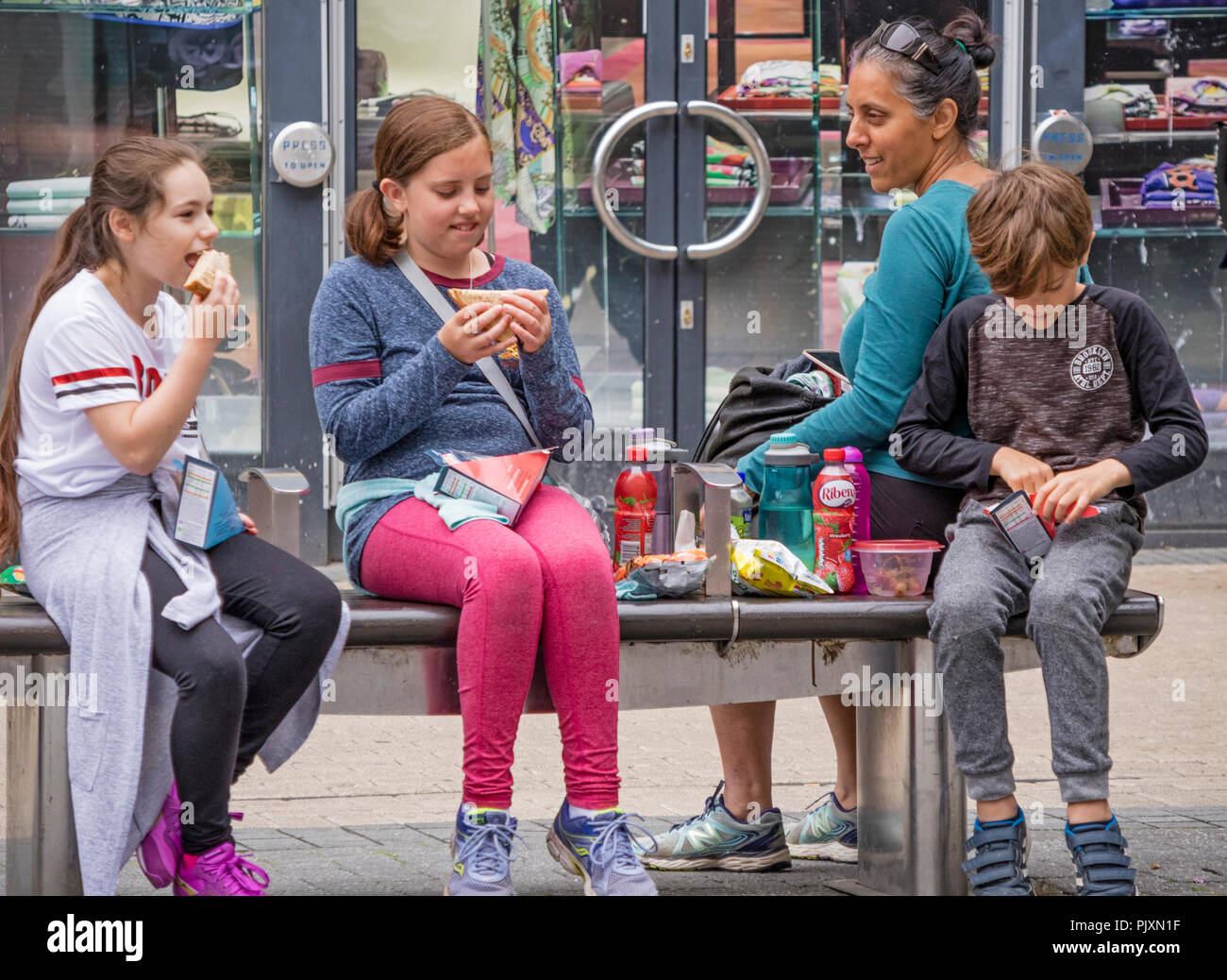 Children eating shop bought fast food while shopping in Bristol, England, UK - Stock Image