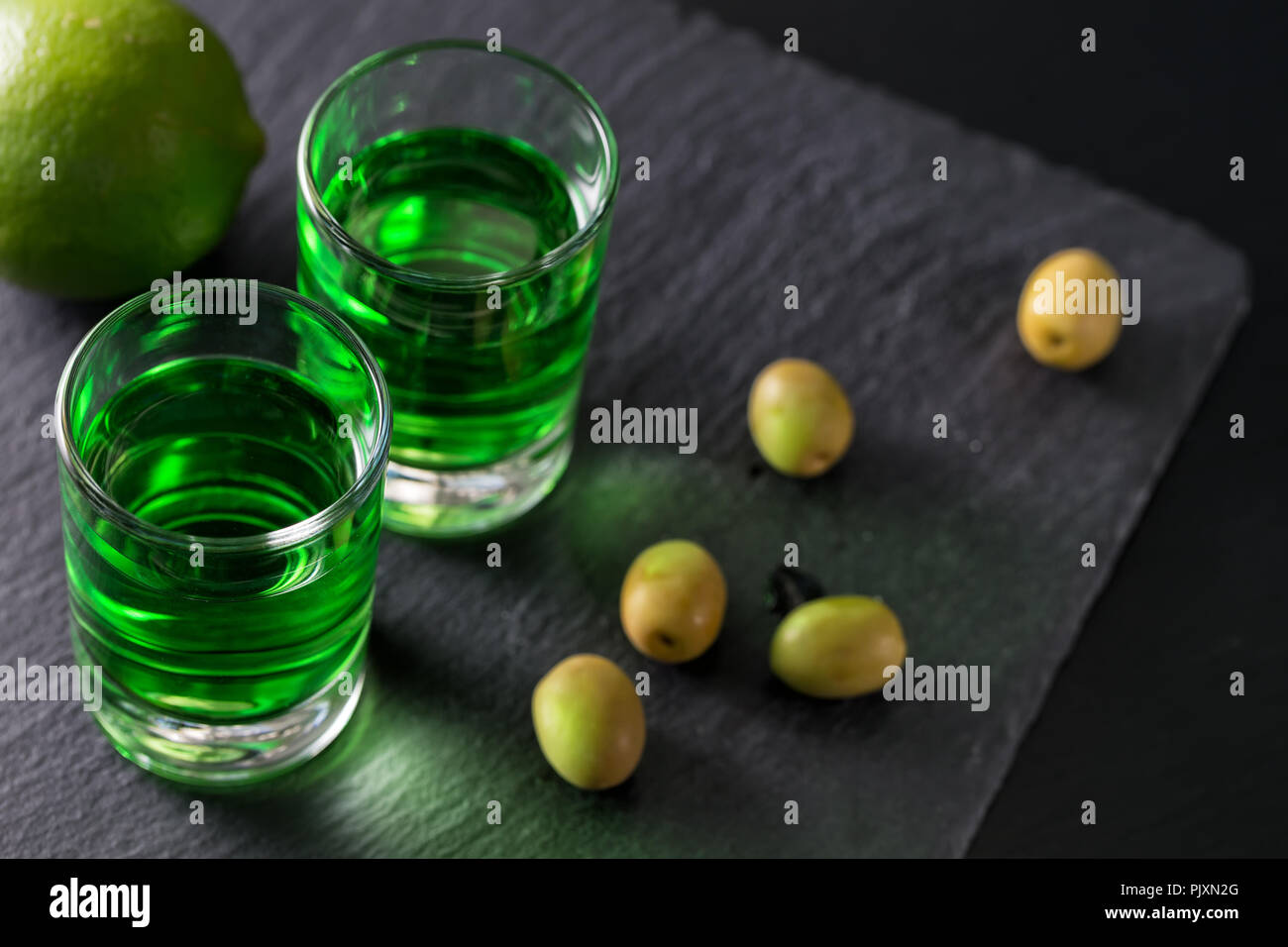 Absinthe with lime and green olives on a dark background - Stock Image