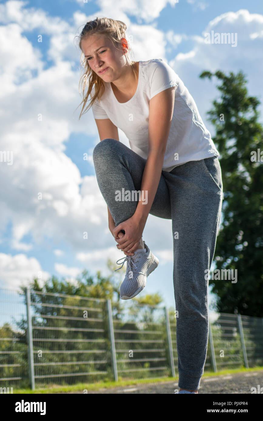 Young woman runner hold her sports injured leg with a painfull face - Stock Image
