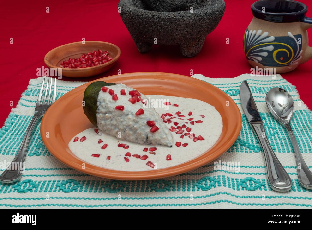 Chile en Nogada is a traditional mexican dish. Poblano pepper stuffed with ground meat, covered in walnut cream and pomgrenade seeds. Stock Photo