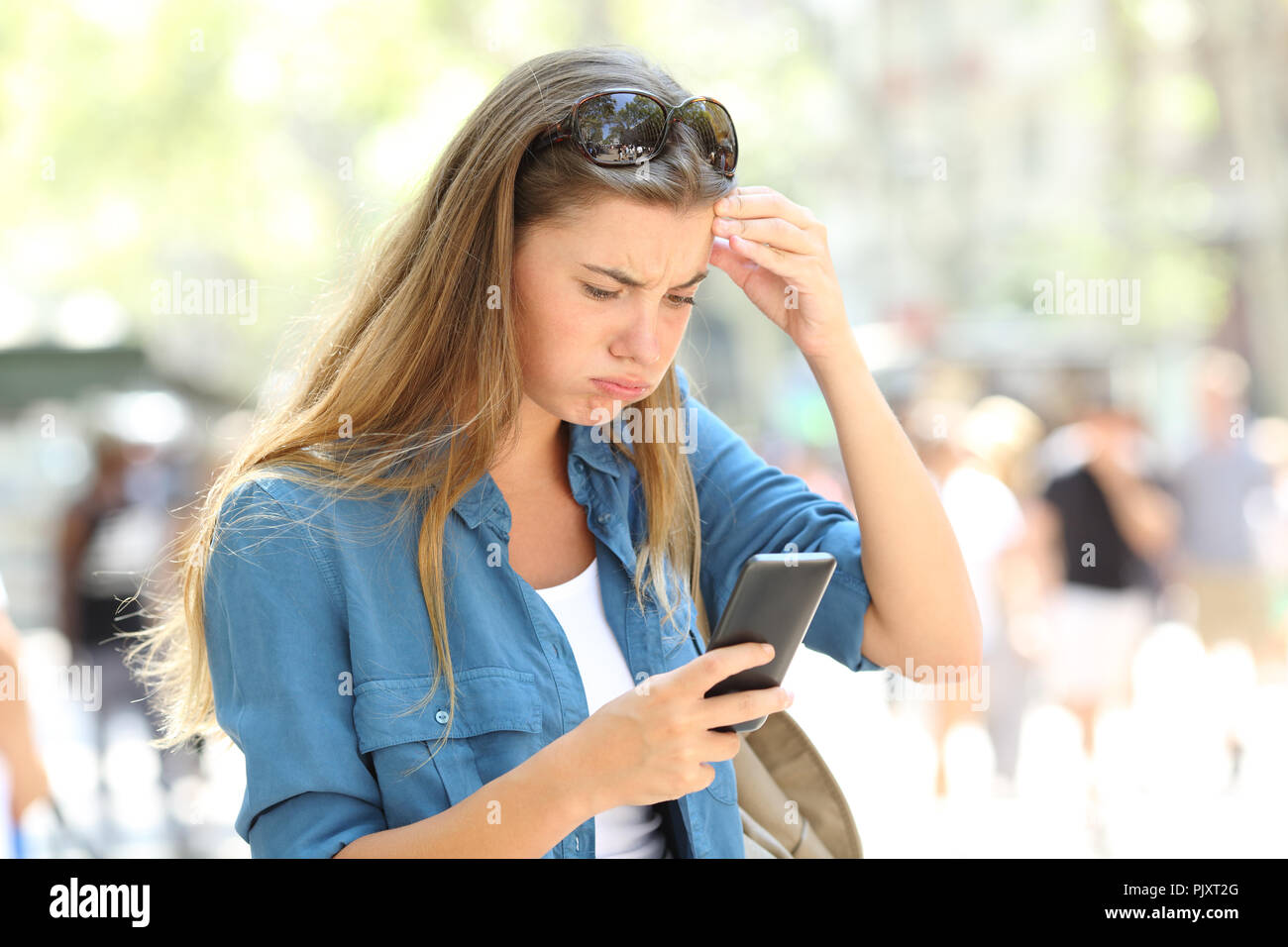 6ad08ff5a79 Frustrated woman reading online smart phone content in the street - Stock  Image