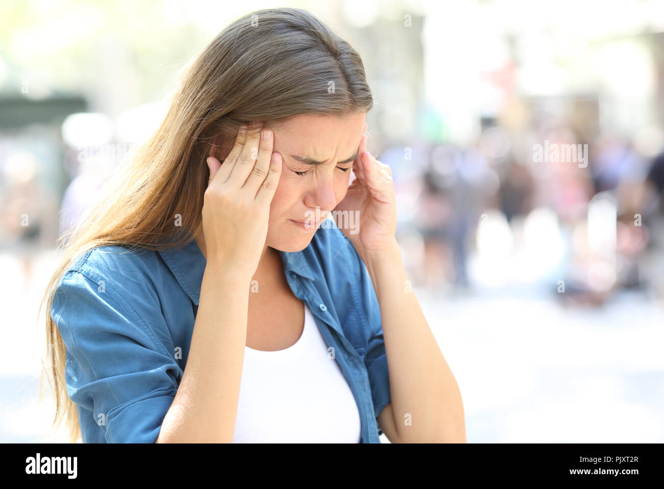 Painful girl suffering migraine touching temple in the street - Stock Image