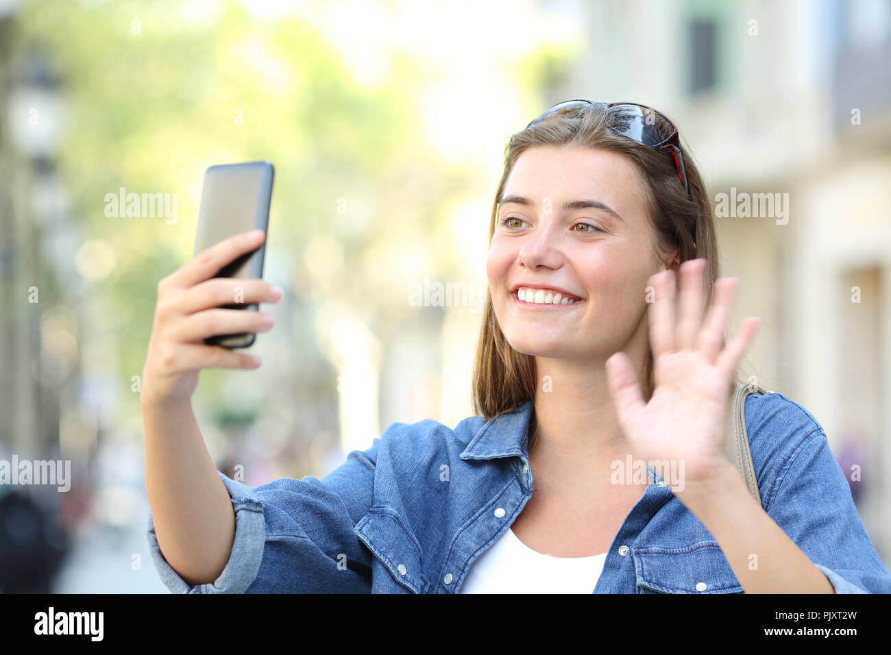 Happy girl waving hand greeting during a phone video call in the happy girl waving hand greeting during a phone video call in the street m4hsunfo