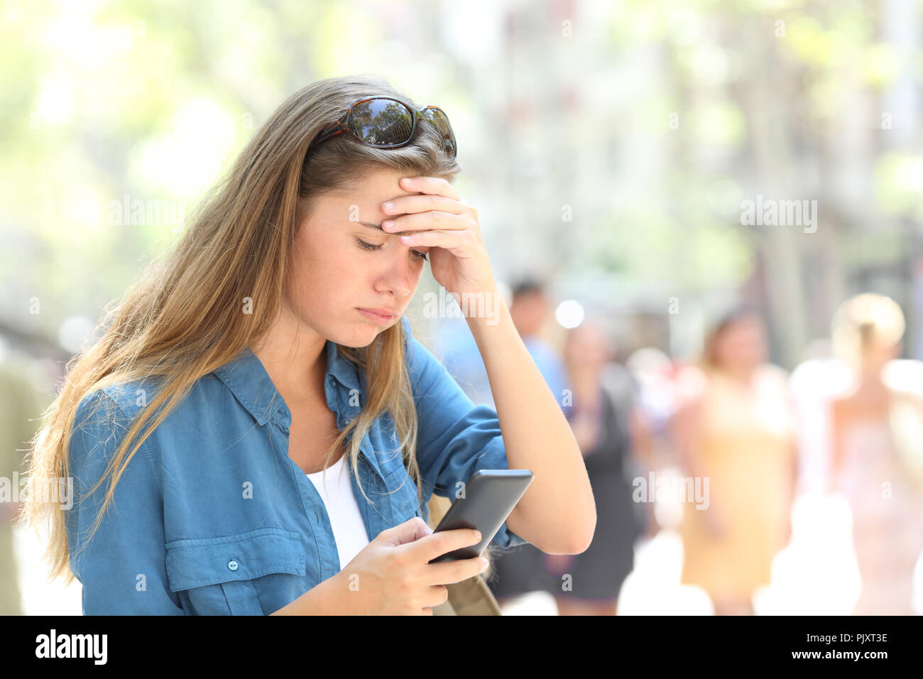 147c4d36f41 Worried woman reading online smart phone content in the street - Stock Image