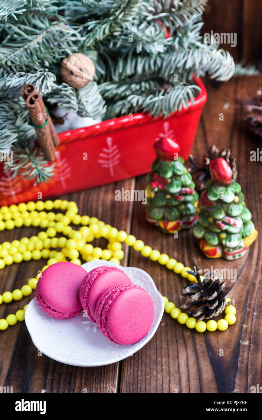 Pink macaroons with christmas decorations on woooden background - Stock Image