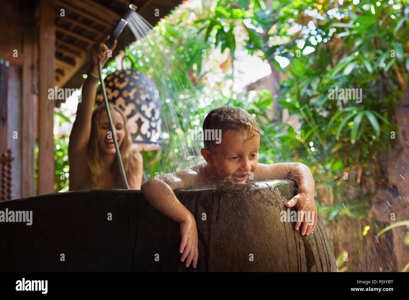 Happy baby son with mother have fun in bath. Playful woman spraying child from shower in outside bathroom on veranda with beautiful tropical garden. - Stock Image