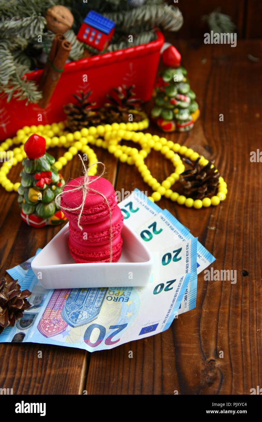 Pink macaroons and twenty euros with christmas decorations on woooden background - Stock Image