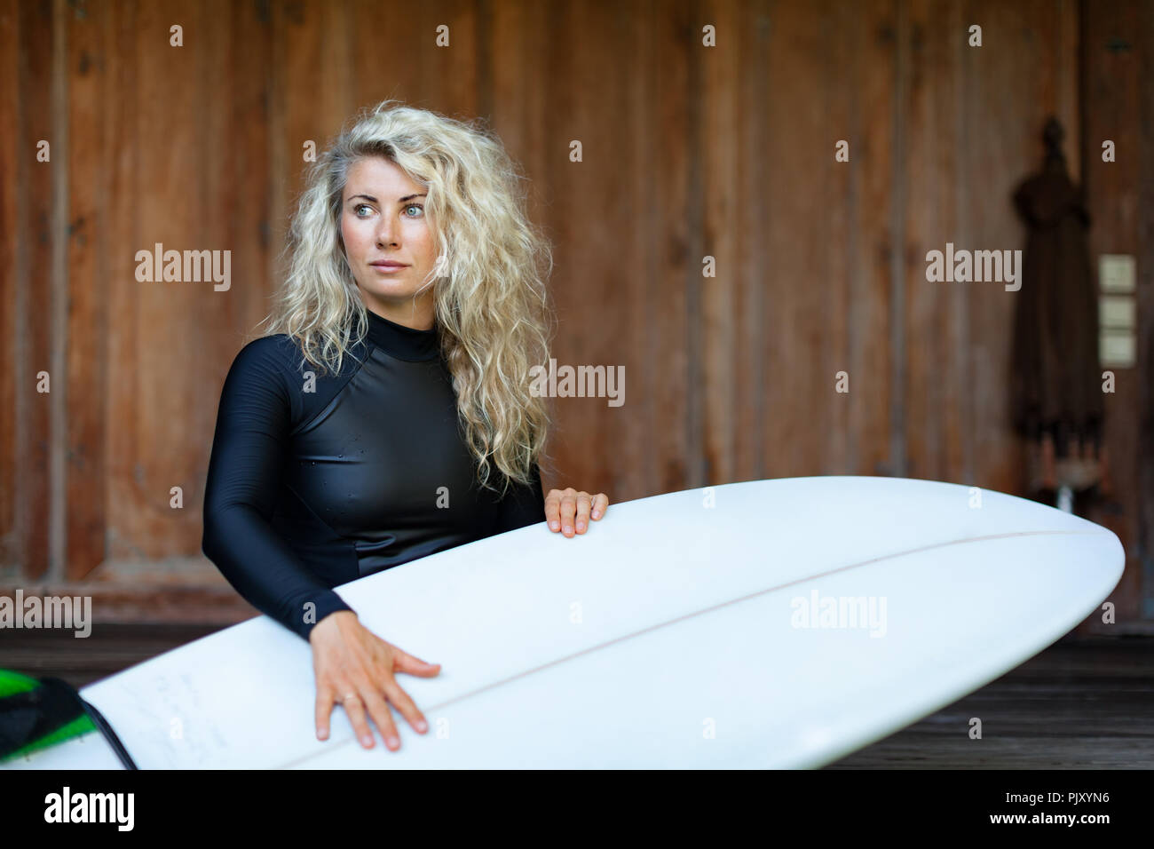 Girl in black wetsuit with surfboard sit on veranda steps of beach villa. Surfer woman look at sea surf and breaking waves. Active people. - Stock Image