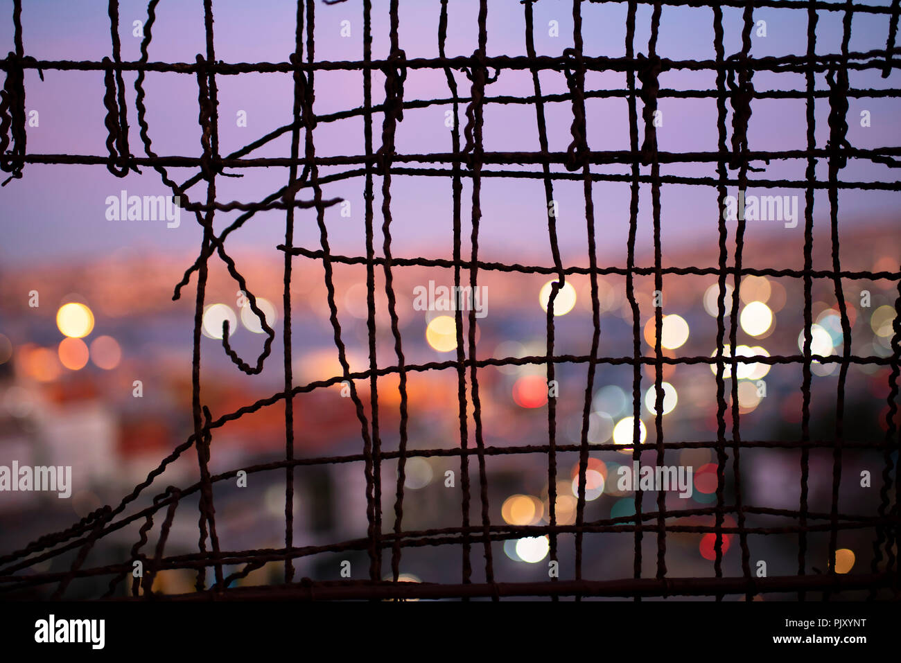 Blurry close up of Valparaiso during dusk through a wire fence. Urban abstract, city view with bokeh lights, wire fence patterns. Valparaiso, Chile - Stock Image